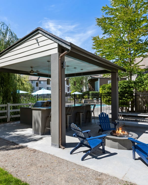 Covered outdoor BBQ and fire-pit lounge at Olin Fields Apartments in Everett