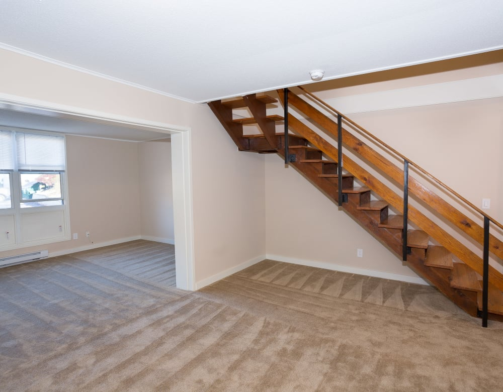 Open stairway leading upstairs from living area at Cortlandt Ridge in Ossining, New York
