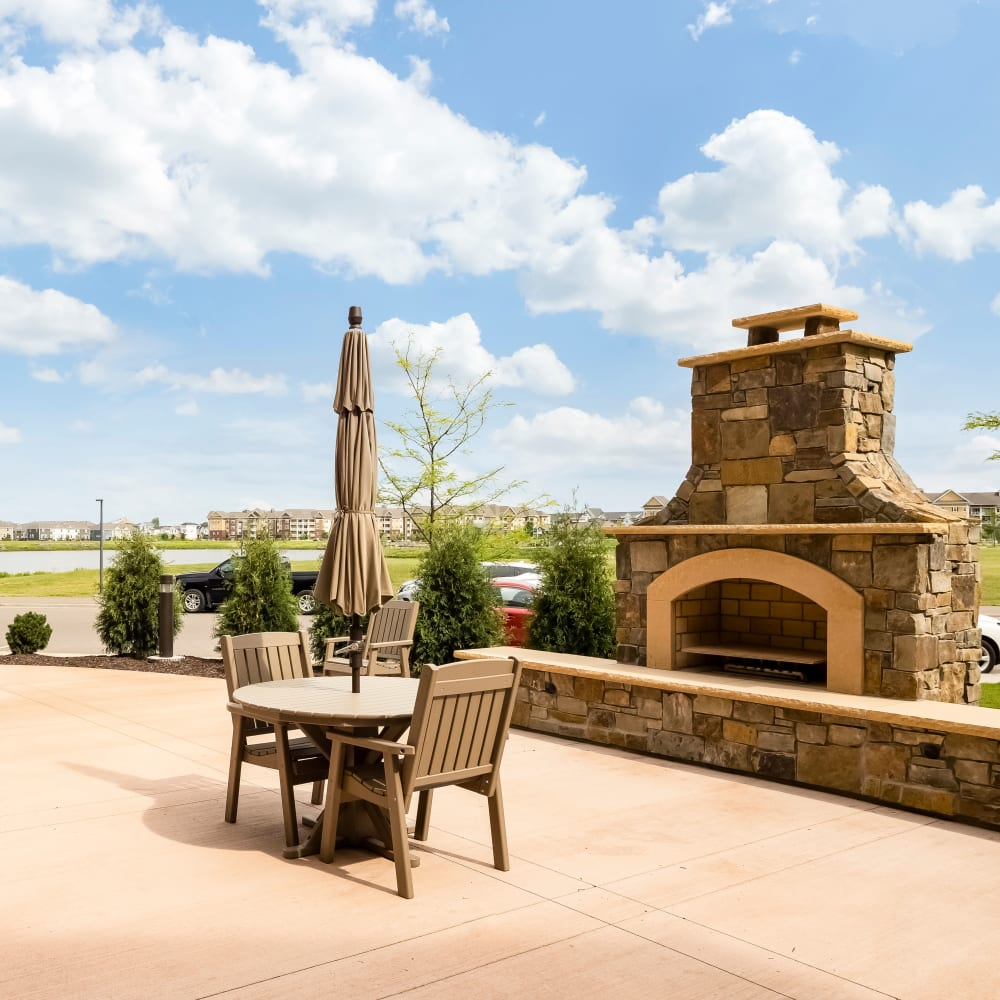 Outdoor community space with fireplace at Applewood Pointe of Maple Grove at Arbor Lakes in Maple Grove, Minnesota.