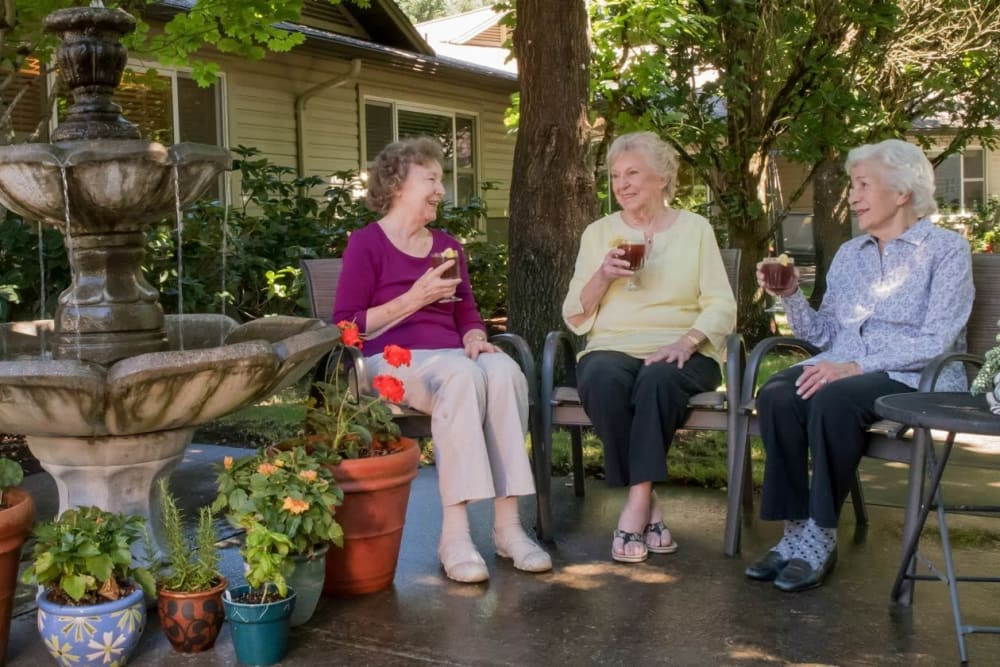 Residents enjoying ice tea near a fountain on outdoor patio at The Springs at Wilsonville in Wilsonville, Oregon