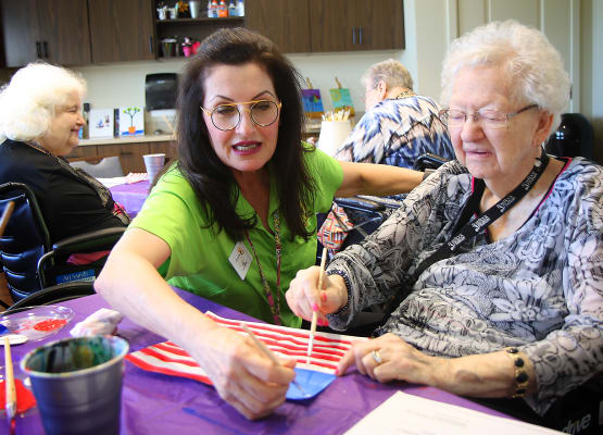Resident and our staff painting flags at Prairie House Assisted Living and Memory Care in Broken Arrow, Oklahoma