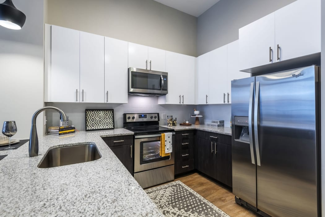 Island and stainless-steel fridge featured in the kitchen at 616 at The Village in Raleigh, North Carolina