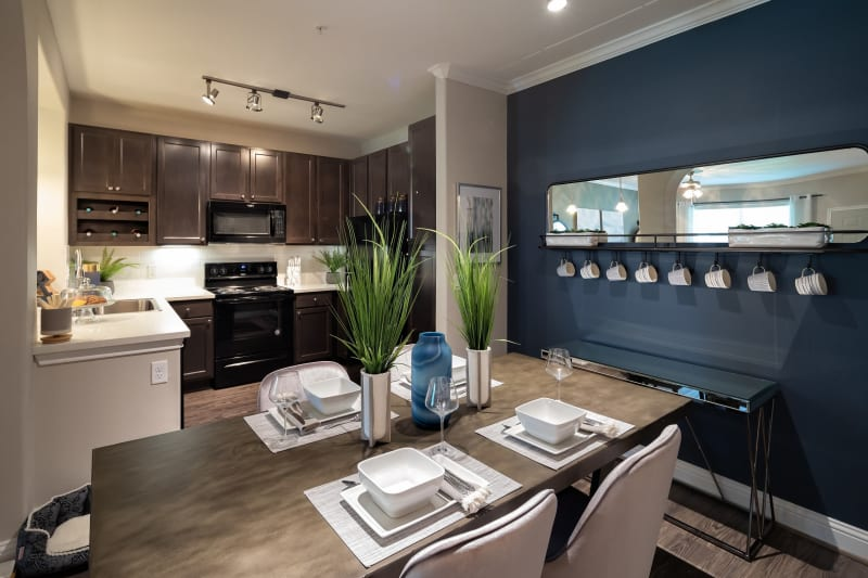 Dining area next to kitchen with hardwood floors and modern decor at The Retreat at Cinco Ranch in Katy, Texas