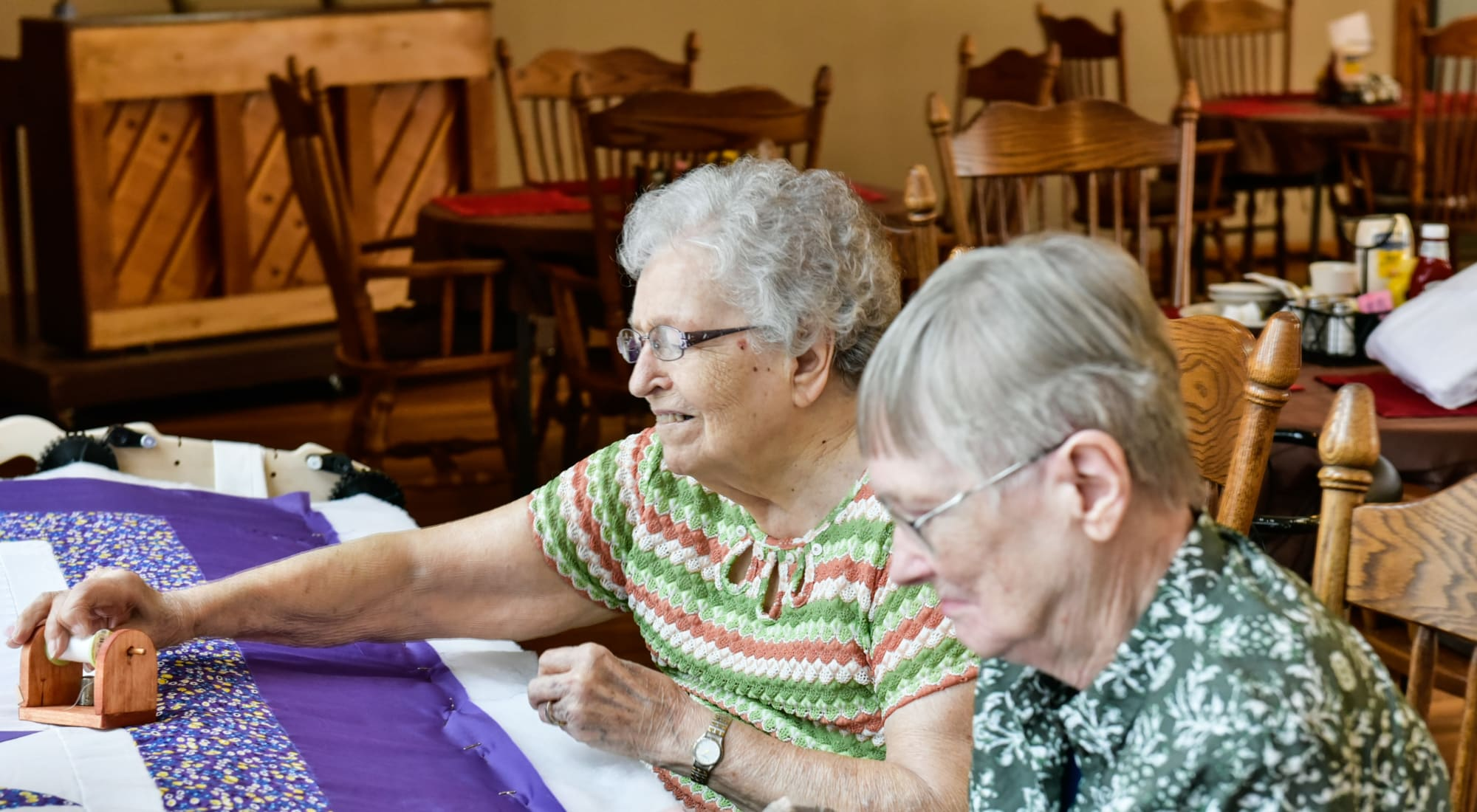 Two resident friends sewing at Garden Place Red Bud