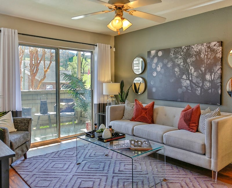 Open-concept living area with hardwood floors and ceiling fan in model home at Allegro on Bell in Antioch, Tennessee
