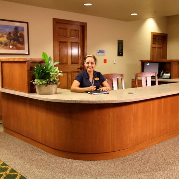 Receptionist sitting at the front desk smiling at the camera at Quail Park Memory Care Residences of Visalia in Visalia, California