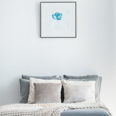 Decorative pillows on the bed with a simple painting of a blue flower hung above in a model home's bedroom at Sofi Belmont Glen in Belmont, California