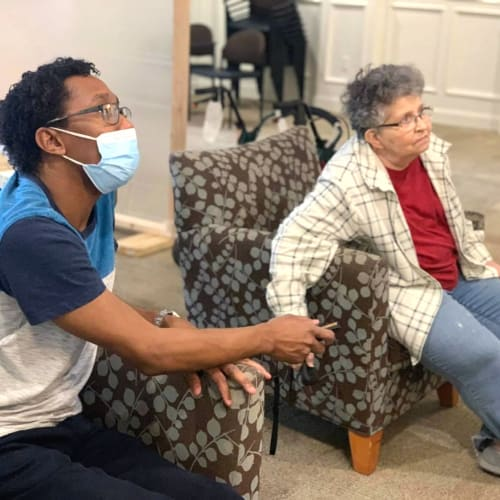 A resident and masked caregiver watching a movie at FountainBrook in Midwest City, Oklahoma
