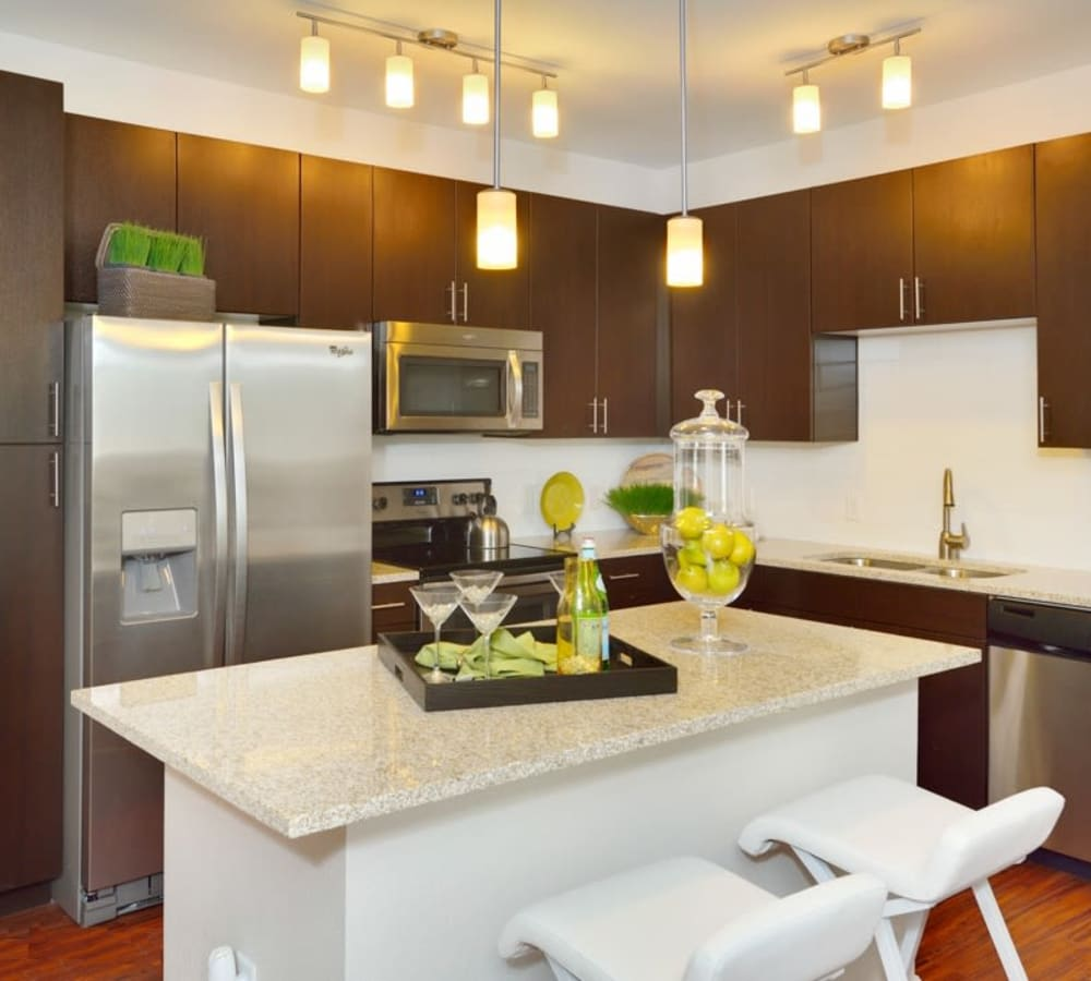 A kitchen with breakfast island at The Parc at Greenwood Village in Greenwood Village, Colorado