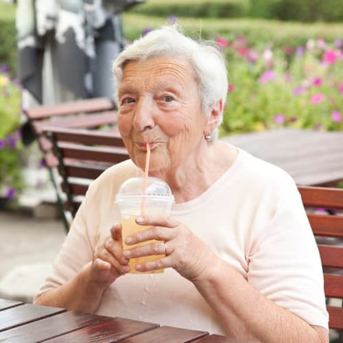 A resident drinking a milkshake at Avenir Memory Care at Scottsdale in Scottsdale, Arizona.