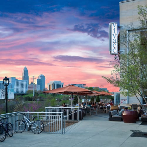 People lounging and eating outside of restaurant at sunset with downtown in background Charlotte, North Carolina near Marq Midtown 205