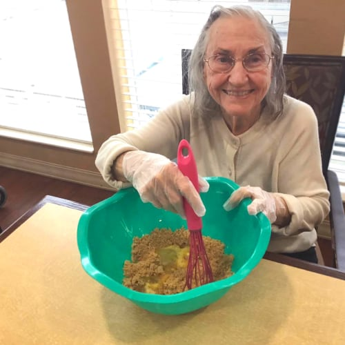 Resident mixing dough at Oxford Glen Memory Care at Grand Prairie in Grand Prairie, Texas