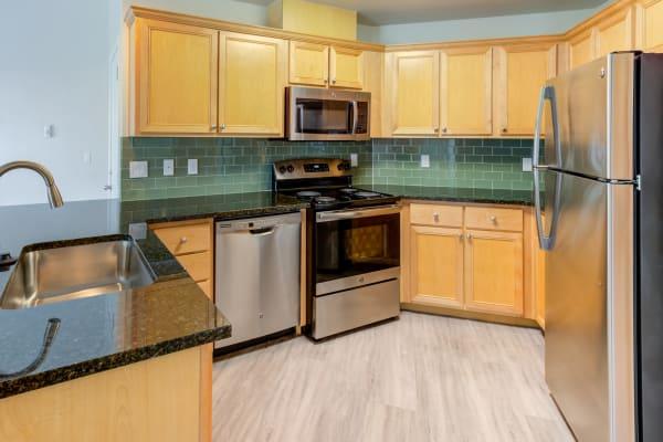 Upgraded kitchen with black appliances and custom tile backsplash at Bradley Park Apartments