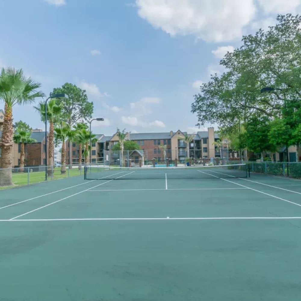 Large outdoor tennis court surrounded by beautiful greenery at Hayden at Enclave in Houston, Texas