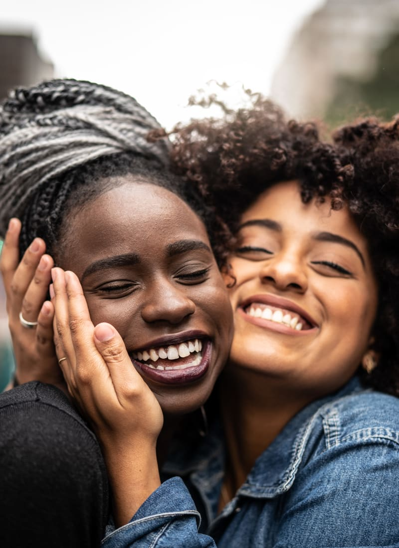 Friends embracing cheek to cheek near Marquis at Carmel Commons in Charlotte, North Carolina