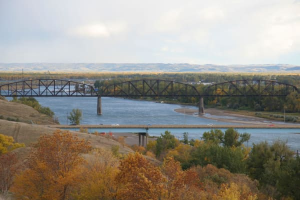 Cars going over a bridge with a river underneath near Touchmark on West Century in Bismarck, North Dakota hiking