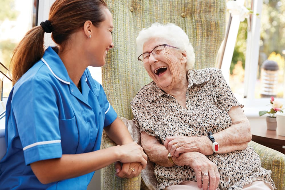 Caregiver and senior woman laughing together