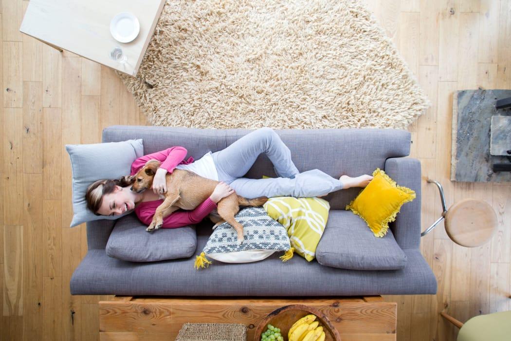 Resident cuddling her puppy in her modern living room at Casanova Monterey in Monterey, California