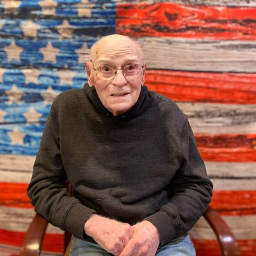 Resident sitting and smiling in front of an american flag at Oxford Glen Memory Care at Owasso in Owasso, Oklahoma