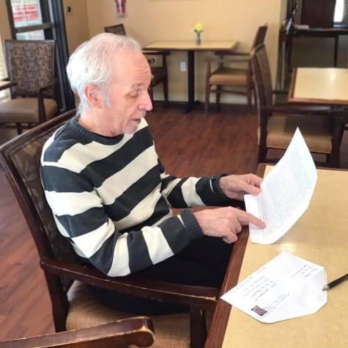 Resident opening a letter at Oxford Glen Memory Care at Grand Prairie in Grand Prairie, Texas