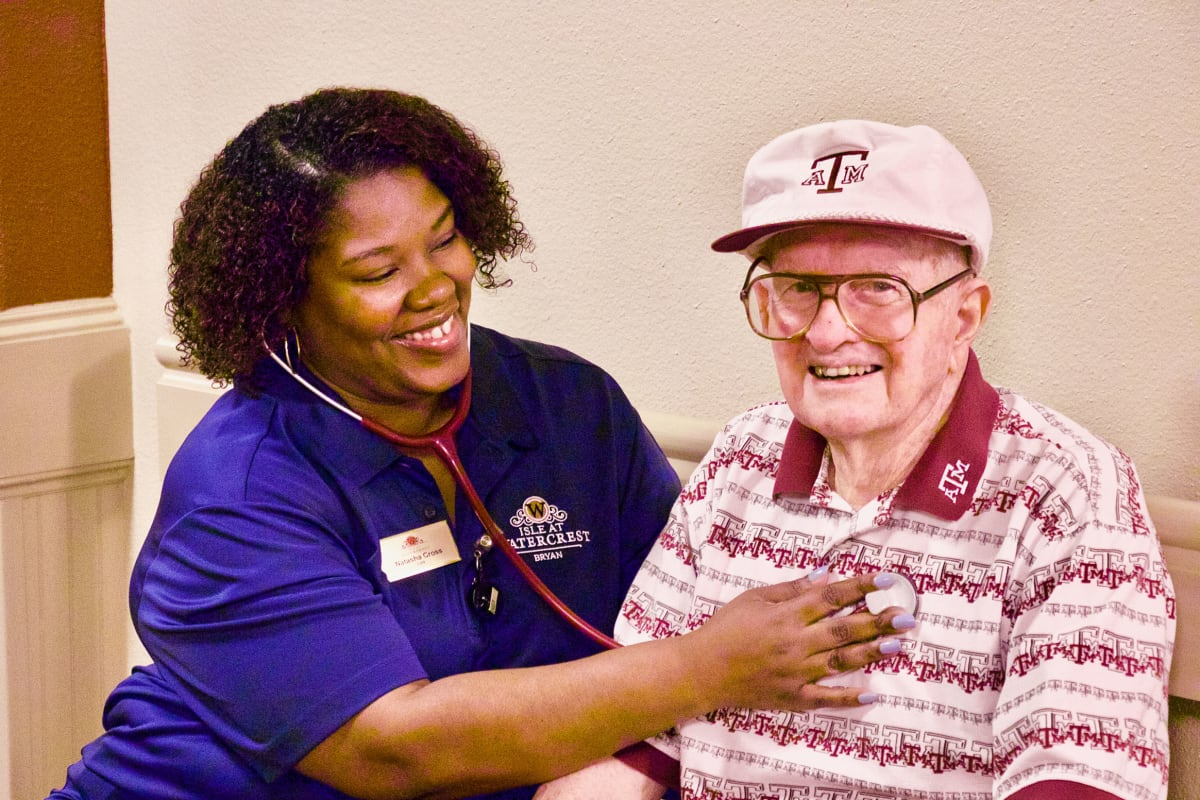 A care taker with a resident at Isle at Watercrest Bryan in Bryan, Texas