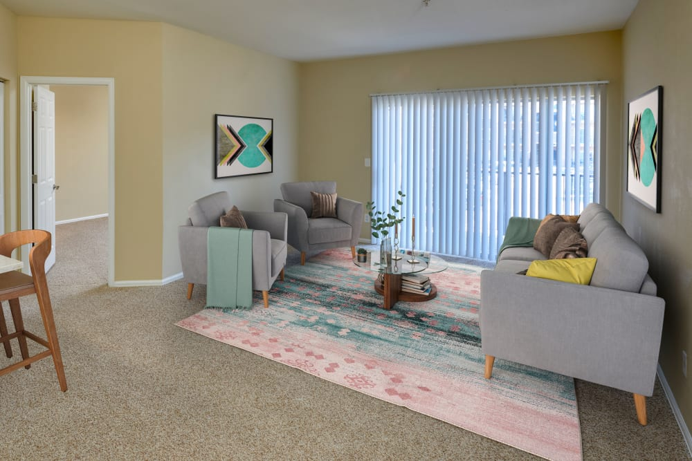 A living room complete with patio access at The Crossings at Bear Creek Apartments in Lakewood, Colorado