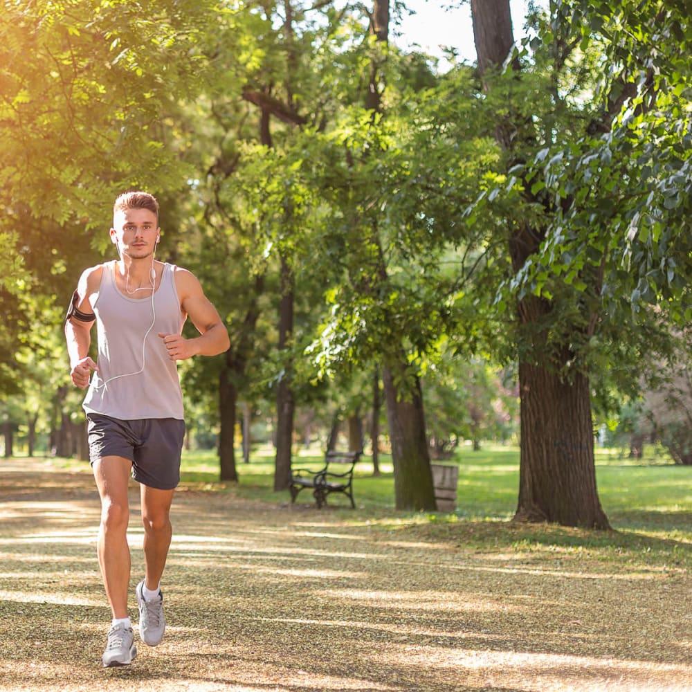 Resident jogging through the verdant neighborhood at Oaks White Rock in Dallas, Texas