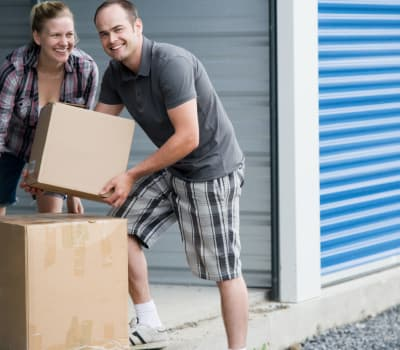 Couple with boxes near self storage units at Hallmark Mini Storage