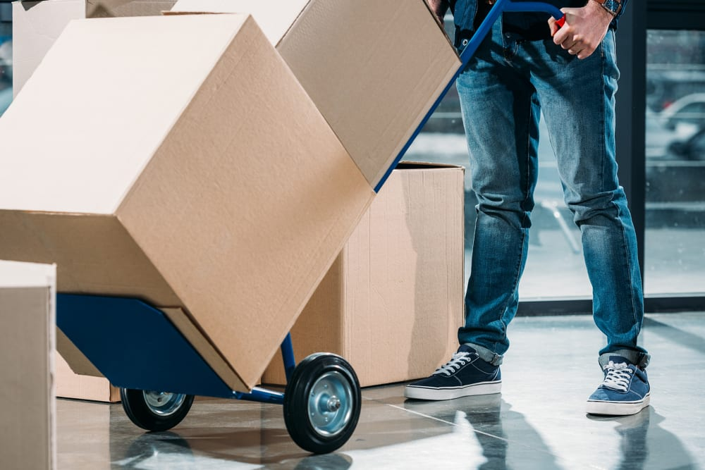Man pushing boxes on a dolly at A-American Self Storage in Lancaster, California