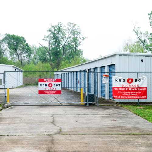 Outdoor storage units with blue doors behind a security fence at Red Dot Storage in Baker, Louisiana