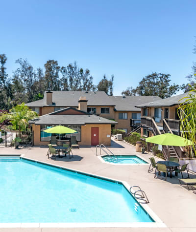 Refreshing swimming pool  with lounge areas and umbrellas at Hillside Terrace Apartments in Lemon Grove