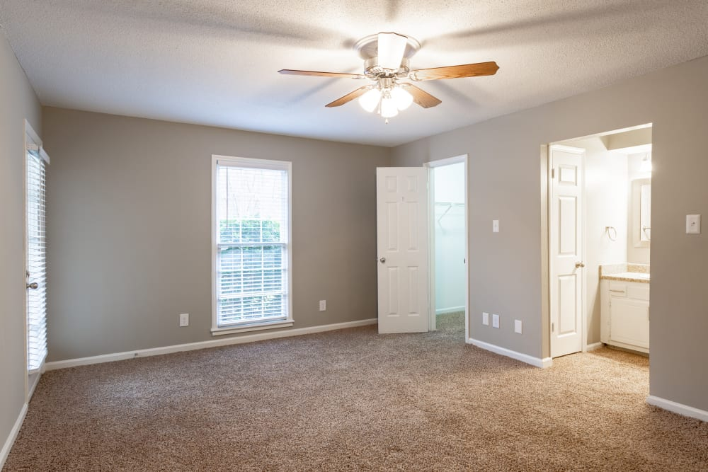 A spacious master bedroom with attached bathroom at The Gatsby at Midtown in Montgomery, Alabama