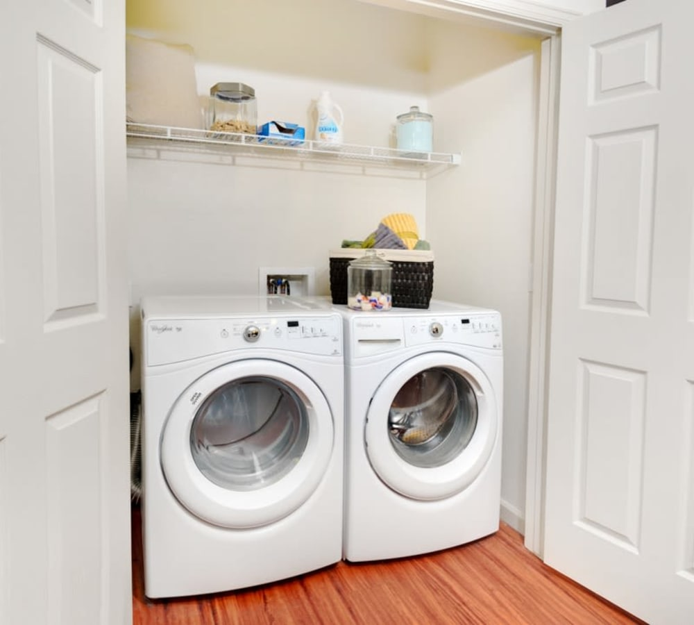 A washer and dryer with shelving at The Parc at Greenwood Village in Greenwood Village, Colorado
