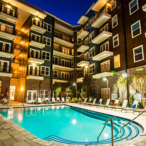 Pool steps overlooking lounge chairs and building units at sunset at Marq Midtown 205 in Charlotte, North Carolina