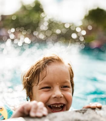 Child enjoying the swimming pool at Alicante Apartment Homes in Aliso Viejo, California