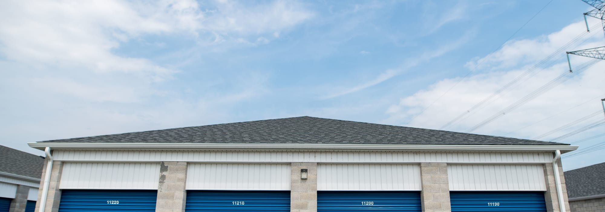 Apple Self Storage - Bowmanville in Bowmanville, Ontario, blue storage unit doors and a sunny sky