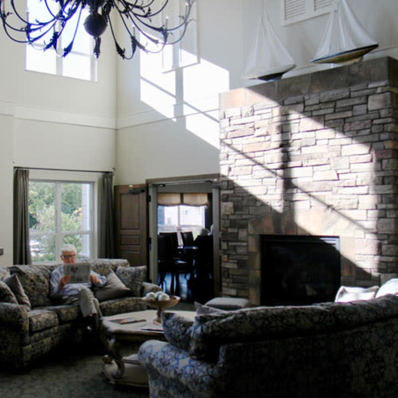 Resident sitting on a couch reading a newspaper in a large fireplace lounge at Deephaven Woods in Deephaven, Minnesota