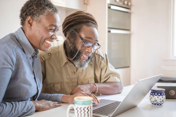 Resident couple browsing the internet on a laptop in their Ebenezer Senior Living apartment