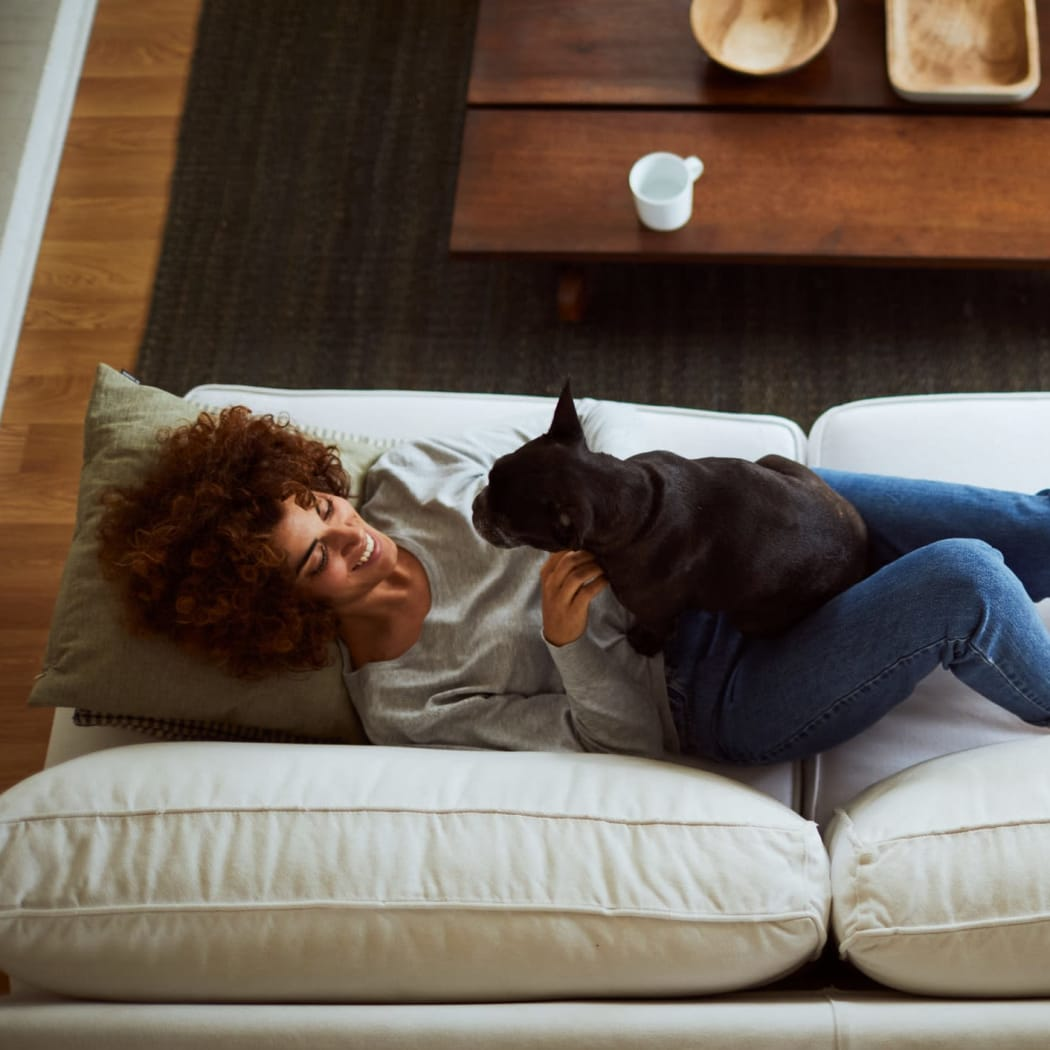 Resident laying on her couch with her dog at Cedar Ridge in Tulsa, Oklahoma