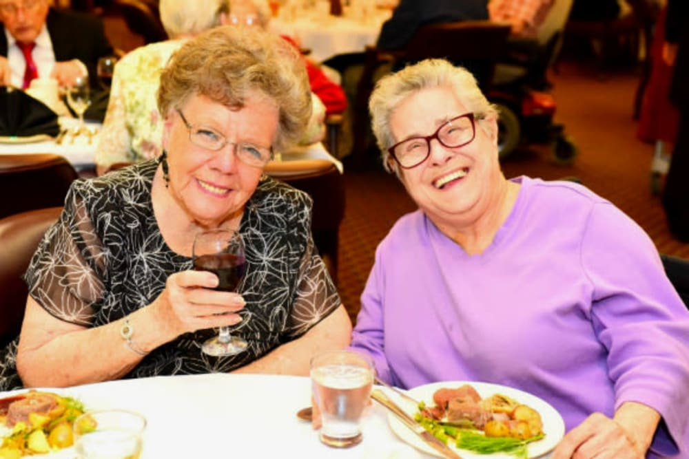 Two residents enjoying a delicious meal at River Commons Senior Living in Redding, California