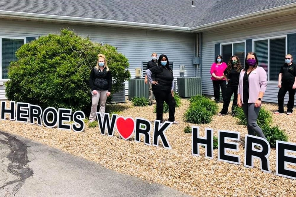 Staff pose outside of building with heros work here sign at Corridor Crossing Place in Cedar Rapids, Iowa