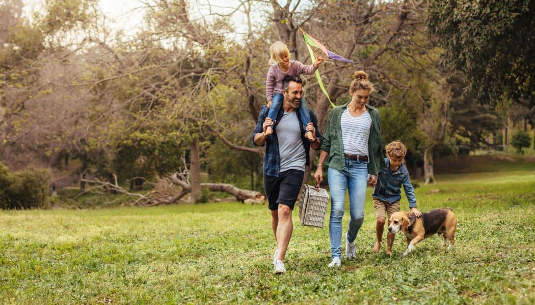 Family walking their dog at a local park in Broken Arrow, Oklahoma near Scissortail Crossing Apartments