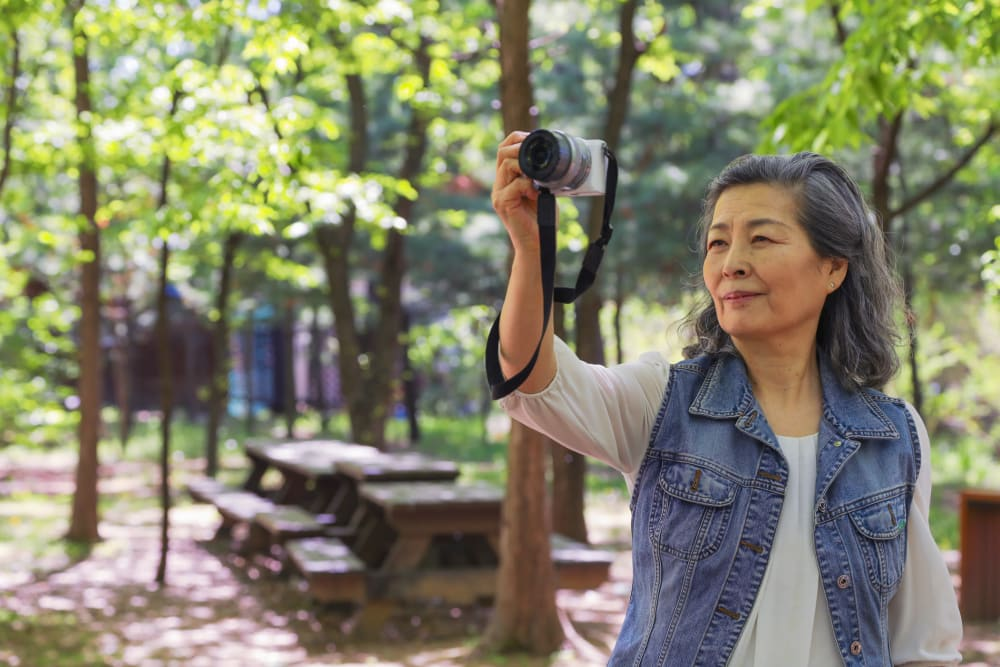 A woman taking pictures in the woods near Applewood Pointe of Westminster in Westminster, Colorado