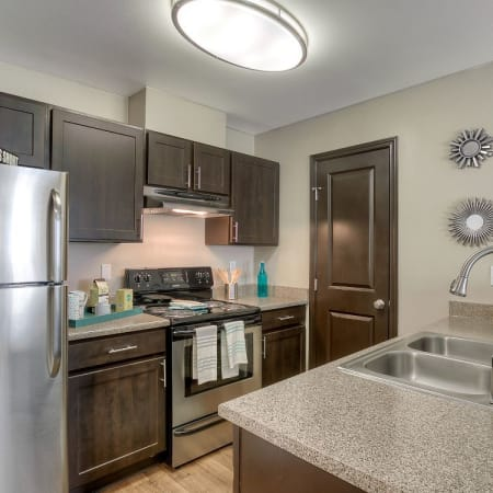 Brown Model Kitchen at Pebble Cove Apartments in Renton