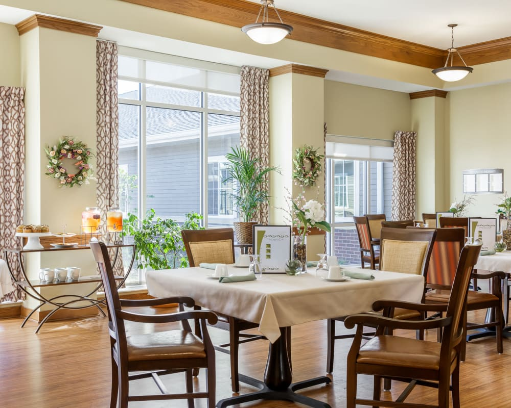 Upscale resident dining room with tall windows and high ceilings at Edencrest at The Legacy in Norwalk, Iowa.