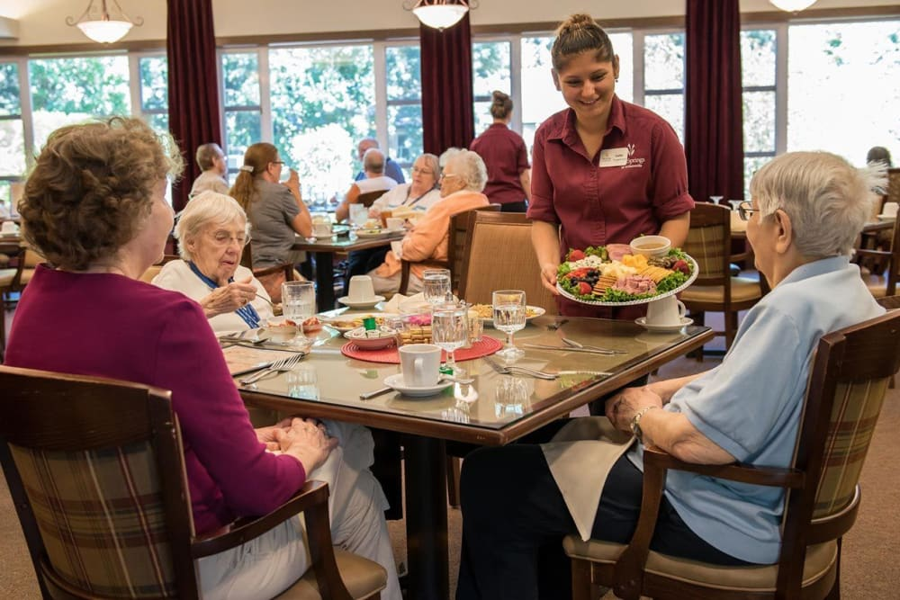 Dinning room server delivers delicious charcuterie board to residents at The Springs at Wilsonville in Wilsonville, Oregon