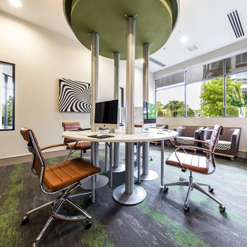 Executive business center with multiple workstations in center of room at Marq Uptown in Austin, Texas
