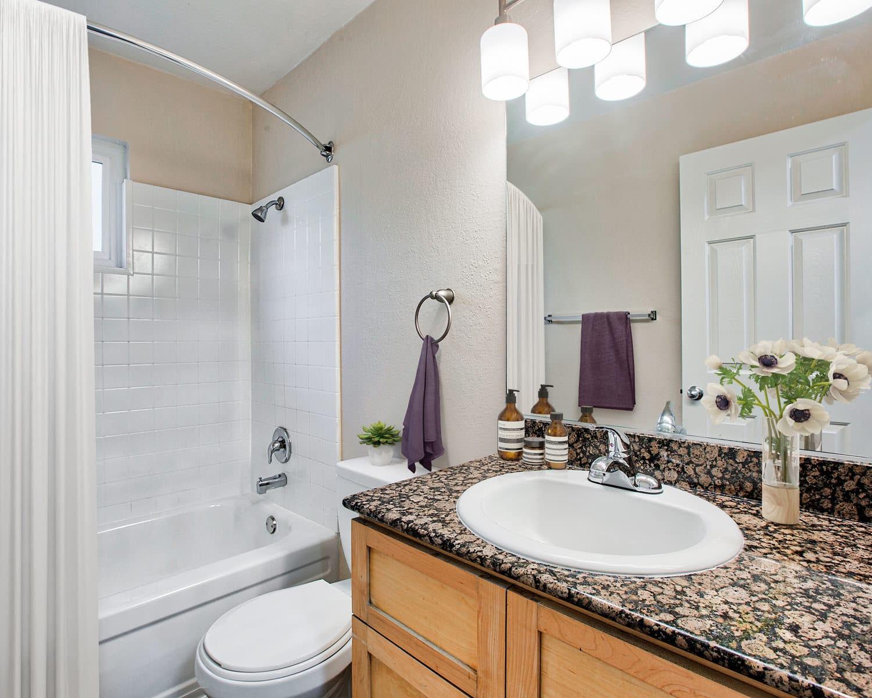 Granite countertop and a large vanity mirror in a model home's bathroom at Pleasanton Place Apartment Homes in Pleasanton, California
