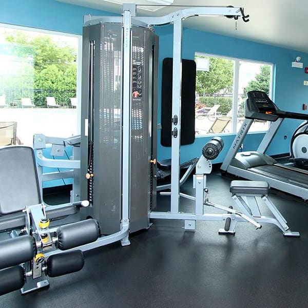 Fully-Equipped fitness center with large windows and view of pool at West Line Apartments in Hanover Park, Illinois