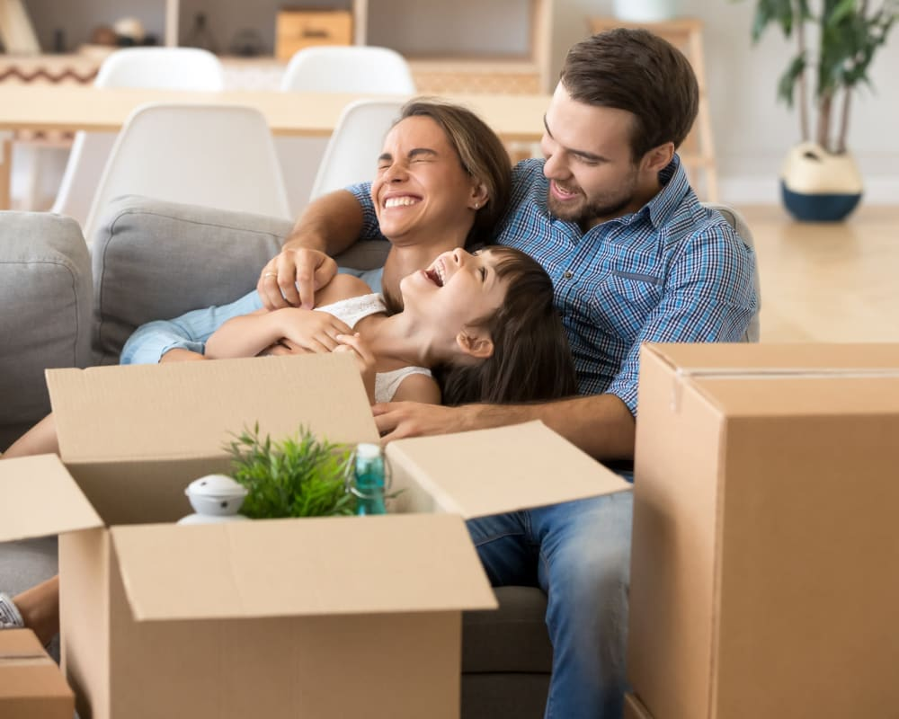A happy family taking a break from packing boxes to be move to a STOR-N-LOCK Self Storage location